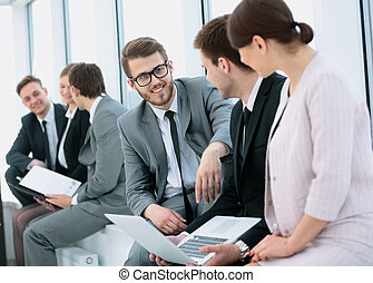 business team with laptop and papers sit and talk in the...