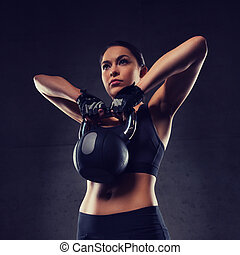 young woman flexing muscles with kettlebell in gym -...