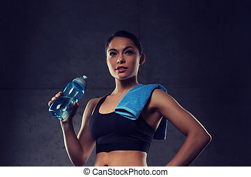 woman with towel drinking water from bottle in gym -...