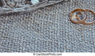 wedding rings and flowers on a linen background.