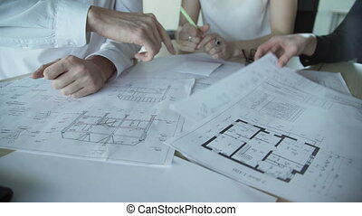 Close up hands of three workers discussing building drawings...