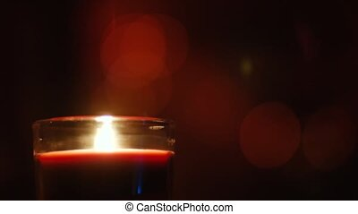 Candles burning on a background of twinkling garlands in the darkness