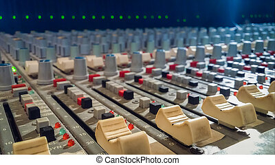 Professional audio mixing console with faders in recording...