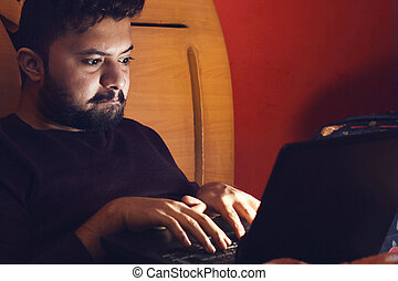 Young hacker looking at laptop and getting in dark room