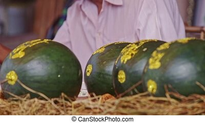 Decorated Watermelons on Market Counter against Man in...