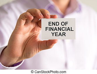 Businessman holding a card with END OF FINANCIAL YEAR...