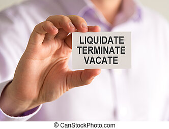 Businessman holding a card with LIQUIDATE, TERMINATE, VACATE...