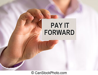 Businessman holding a card with PAY IT FORWARD message