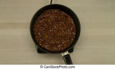 View on cook stirs beans and meat during cooking -...