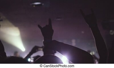 Fans waving their hands and hold the phone with digital displays the crowd at a rock concert in night club in slow motion.