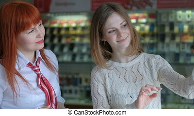 Beautiful girl choosing a new mobile phone in a shop. The...
