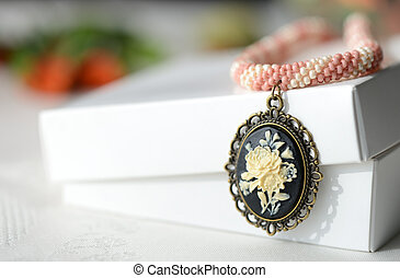 Short beaded necklace with rose cameo pendant close up