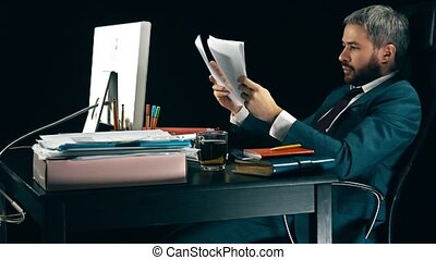 Frustrated bearded businessman looks through business papers...