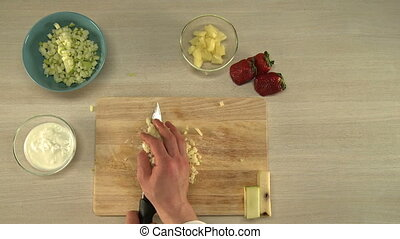 Cooking of fruit salad. First-person view on chef cutting...