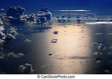 Night flight over the sea - Aerial view of sea and cumulus...