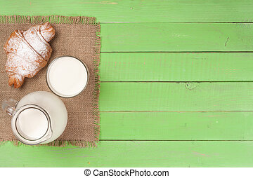 jug and glass of milk with croissants on a green wooden background with copy space for your text. Top view