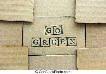 Cardboard card with words Go Green made by black alphabet stamps