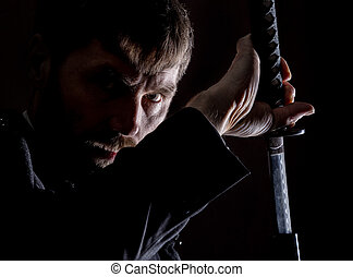 stern angry businessman in a wool coat with sword in dark...