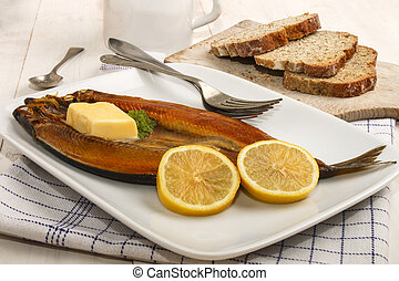 smoked kipper with lemon, butter and parsley on a plate