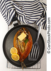 smoked kipper with lemon, butter and parsley on a pan
