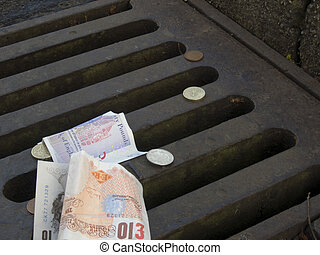 Money down the drain - Conceptual image of bank notes and...