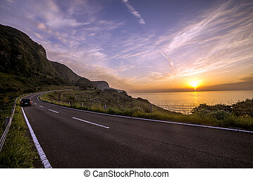 Evening roadway in front of sea with sinking sun in...