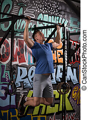 man doing pull ups - strong young man doing pull ups on a...