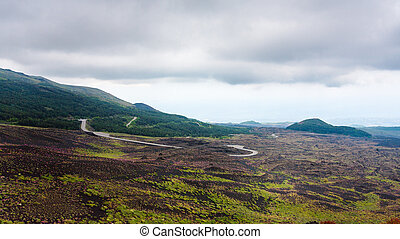 cloudy sky over road in lava fields on Mount Etna - travel...