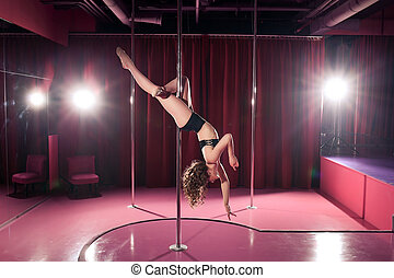 Beautiful girl performs tricks on a pylon on a pink background