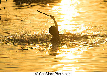The child is swimming at sunset.