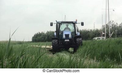Mowing the lawn with tractor in the fields - Farmer mows the...