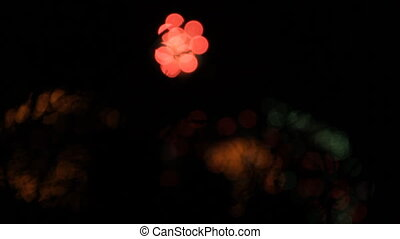 White, red, green and orange balls of fireworks opening one from another. Bokeh.