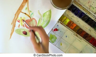A young girl draws watercolor paint on a white sheet of paper. Using a brush. Top view. At school.