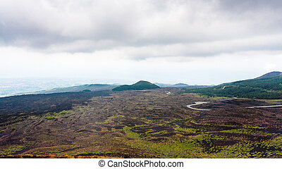 low cloudy sky over lava fields on Mount Etna - travel to...