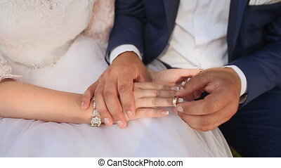 The newlyweds are putting each other's wedding rings on...