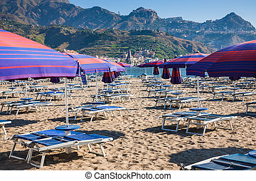 Parasols and beds on urban beach in giardini naxos