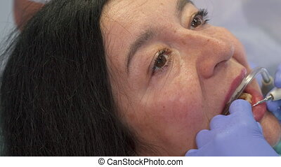 Woman gets deep dental cleaning - Senior caucasian woman...