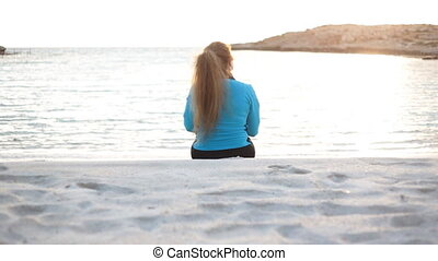 Beautiful fitness woman sitting and resting on sea beach