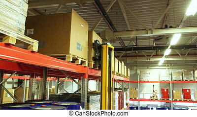 Worker using a forklift truck working inside a storage...