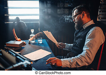 Bearded writer smokes and reads handwritten text -...
