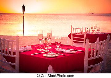 sunset beach dinner - Table on beach set for romantic sunset...