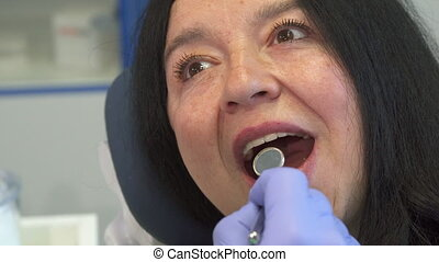 Woman opens her mouth for dental check up - Senior caucasian...