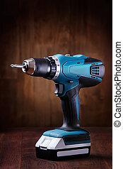 Blue cordless screwdriver with a drill on wooden table with...