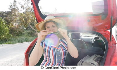 Young woman with suitcase in car trunk