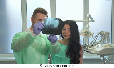 Dentist explaines to the patient something on x-ray