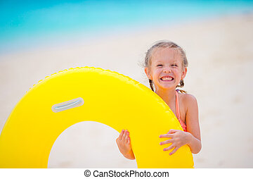 Little girl with inflatable rubber circle on white beach at...