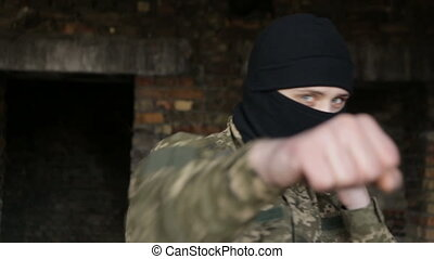 A man in camouflage practices strikes on an abandoned...