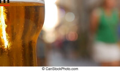 Glass of beer stands on tray against city street traffic.