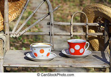 Rustic still life with a cups of tea and straw hats - A...