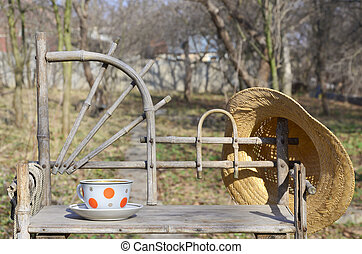 Rustic still life with a cup of tea and straw hat - A rustic...